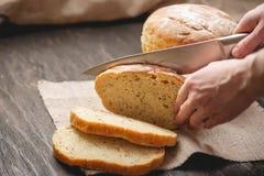 Les mains ont coupé avec du pain frais naturel fait maison de couteau avec une croûte d'or sur le fond en bois Produits de cuis photo stock