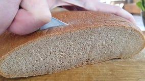 Les mains ont coupé le pain avec un couteau sur une nutrition en bois de consommation banque de vidéos