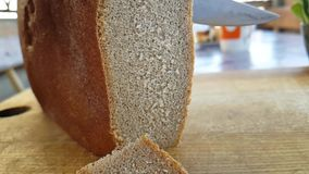 Les mains ont coupé le pain avec un goût de couteau sur une nutrition en bois de consommation banque de vidéos