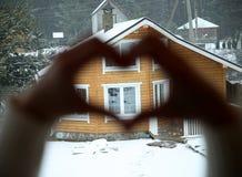 Les mains ont effectué la forme du coeur, et la maison sur l'hublot Images stock