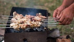 Les mains ont mis des kebabs sur un barbecue Photographie stock libre de droits