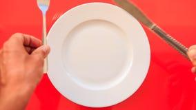 Les mains ont mis le couteau de fourchette en travers sur le plat sur le Tableau rouge banque de vidéos