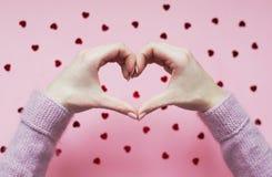 Les mains ont plié le coeur sur le fond rose avec les coeurs rouges photographie stock
