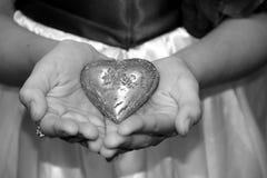Les mains ouvertes de jeune fille tenant le coeur Image stock