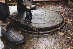 Les mains ouvre la trappe d'égout par le montage Image libre de droits