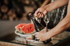 Les mains ouvrent la bouteille de champagne Pastèque et fruit arrières Images stock