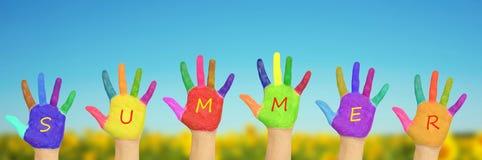 Les mains peintes de l'enfant contre le ciel bleu Photographie stock libre de droits