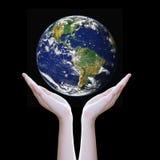Les mains protègent la terre, éléments de cette image meublés par la NASA Photo libre de droits