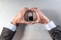 Les mains protectrices d'homme d'affaires dans l'amour avec la protection des données creusent le symbole Photographie stock
