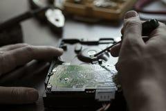 Les mains réparent l'unité de disque dur Images stock