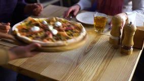 Les mains regardent des couples en pizza commandée de attente de restaurant banque de vidéos