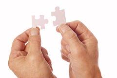 Les mains relient des morceaux de puzzle denteux Images stock