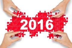 Les mains s'chargent du puzzle avec les numéros 2016 Photo stock