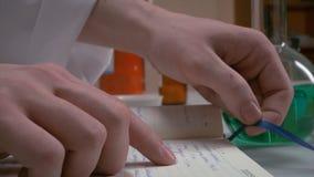 Les mains s'ouvrent et regardant quelque chose dans un journal intime, carnet mains de l'écriture de scientifique sur le carnet,  Photographie stock libre de droits
