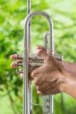 Les mains saisissent la trompette Image libre de droits