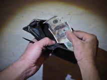 Les mains sales d'hommes tiennent dans ma main un vieux portefeuille battu et une facture de $ brûlée par bourse 100 sur le fond  Photos libres de droits