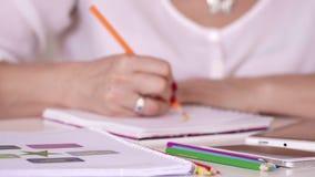 Les mains se ferment vers le haut Belle fin rouge de manucure  La femme souligne les détails importants avec les crayons colorés  banque de vidéos