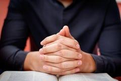 Les mains se sont pliées dans la prière sur une Sainte Bible dans le concept d'église pour la foi, le spirtuality et la religion photo libre de droits