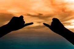 Les mains silhouettent sous le coucher du soleil Image stock