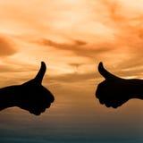 Les mains silhouettent sous le coucher du soleil Photos stock