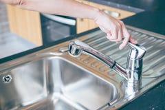 Les mains sont l'eau étroite de chrome de robinet photo libre de droits