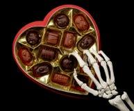 Les mains squelettiques choisit un chocolat images stock