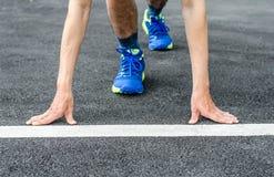 Les mains sur la ligne de départ, le coureur masculin est sur le point de commencer à courir Photographie stock libre de droits