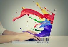 Les mains sur le clavier avec coloré éclabousse hors du moniteur Photos stock