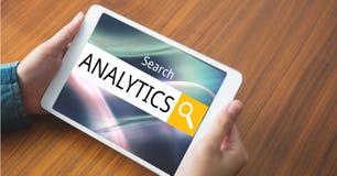 Les mains tenant la tablette avec l'analytics textotent dans la boîte de recherche photographie stock