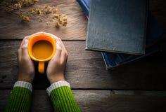 Les mains tenant la tasse de café et incluent les livres, smartphone sur le fond en bois Ton de vintage Images stock