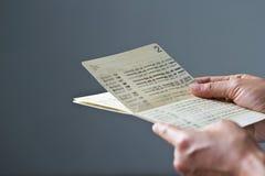 Les mains tenant le carnet bancaire d'économie, réservent l'obscurité sur le fond gris Images libres de droits