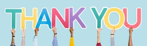 Les mains tenant les mots vous remercient image stock