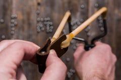 Les mains tenant une fronde étirée, préparent pour le tir avec une boule en métal, sur le fond d'une vieille barrière en bois Photos stock
