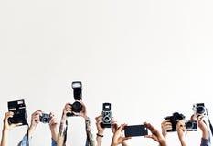 Les mains tiennent des appareils-photo avec le fond blanc photographie stock libre de droits