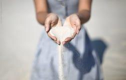 Les mains tiennent des sables sur la plage, sable verse vers le bas des mains photo libre de droits