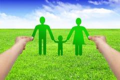 Les mains tiennent la famille de papier sur l'herbe, concept d'eco Photographie stock