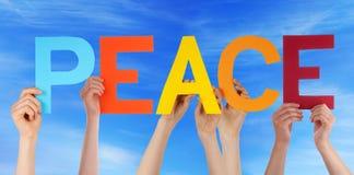 Les mains tiennent le ciel bleu de paix droite colorée de Word Image stock