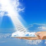 Les mains tiennent le PC de comprimé avec des escaliers en ciel Image libre de droits
