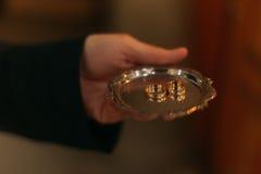 Les mains tiennent le plat avec des anneaux de mariage d'or photos libres de droits