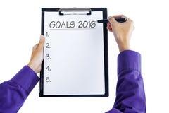 Les mains tiennent le presse-papiers pour écrire des buts d'affaires en 2016 Images stock