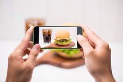 Les mains tiennent le smartphone prenant la photo de l'hamburger fait maison de BBQ Photos libres de droits