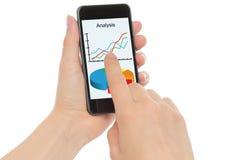Les mains tiennent le téléphone intelligent avec des graphiques photo stock