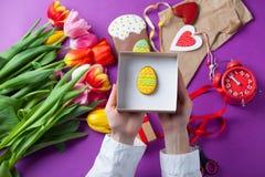 Les mains tiennent un boîte-cadeau avec des oeufs de pâques Photographie stock