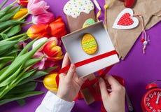 Les mains tiennent un boîte-cadeau avec des oeufs de pâques Photo libre de droits