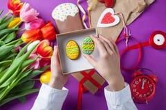 Les mains tiennent un boîte-cadeau avec des oeufs de pâques Image stock