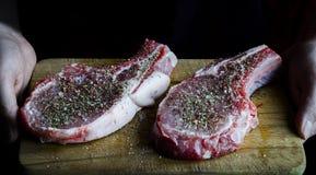 les mains tiennent un conseil sur lequel sont deux biftecks crus de porc arrosés avec des épices et prêts à cuisiner photo stock