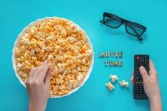 Les mains tient le maïs éclaté et l'extérieur de TV, le bol de maïs éclaté et le glasse 3D Images libres de droits