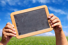 Les mains tient un tableau noir d'ardoise avec l'espace publicitaire Image libre de droits