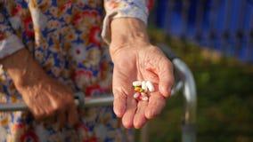 Les mains très de dame âgée prenant des pilules, se ferment d'une femme agée remettent son médicament, problèmes de santé à une v clips vidéos