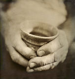 Les mains utilisées de l'homme tenant la tasse en céramique japonaise criquée Photographie stock